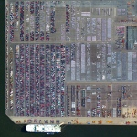 Automobiles and semi-trailer trucks are unloaded and shipped at the Port of Antwerp in Belgium