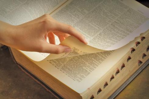 womans-hand-turning-dictionary-pages