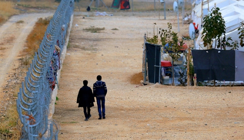 Two Syrian refugees walk along fences in Nizip refugee camp