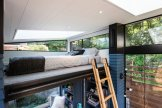 accessed-via-collapsible-ladder-the-58-square-foot-loft-bedroom-with-a-queen-mattress-is-located-beneath-an-angled-tongue-and-groove-cedar-ceiling-thats-painted-white-and-punctuated-by-a