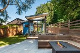 concrete-pavers-line-the-new-hardscape-which-steps-up-to-a-deck-built-of-ipe-wood-ipe-wood-has-also-been-used-for-the-built-in-benches-and-fencing