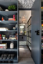 the-entrance-to-the-bathroom-is-tucked-between-two-bookshelves