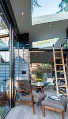 the-gray-blue-siding-continues-from-the-exterior-to-the-interior-to-reinforce-the-seamless-indoor-outdoor-experience-the-callen-chair-and-ottoman-are-from-room-and-board