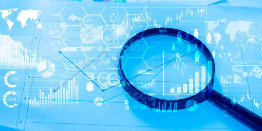 Magnifying glass and documents with analytics data lying on tabl