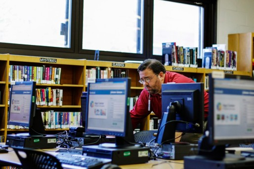 A librarian turns on computers in preparation to teach senior citizens how to set up and use a Facebook account during a class at a branch of the New York Public Library in New York