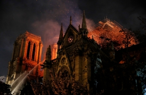 Sparks fill the air as Paris Fire brigade members spray water to extinguish flames as the Notre Dame Cathedral burns in Paris, France, April 15, 2019. REUTERS/Philippe Wojazer