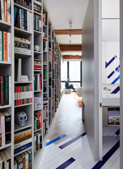 rectangular-blue-and-white-tiles-are-positioned-at-an-angle-in-the-lofts-bathroom-and-continue-onto-the-floor-and-into-the-hallway-adding-a-vibrant-playful-touch